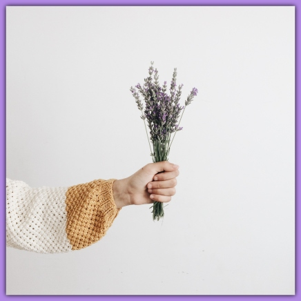 person_in_crocheted_jumper_holds_lavender